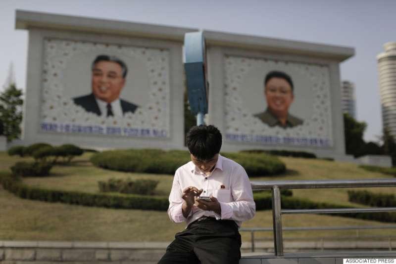 平壤街頭,一名男子在金正日與金日成像前使用手機。(美聯社)