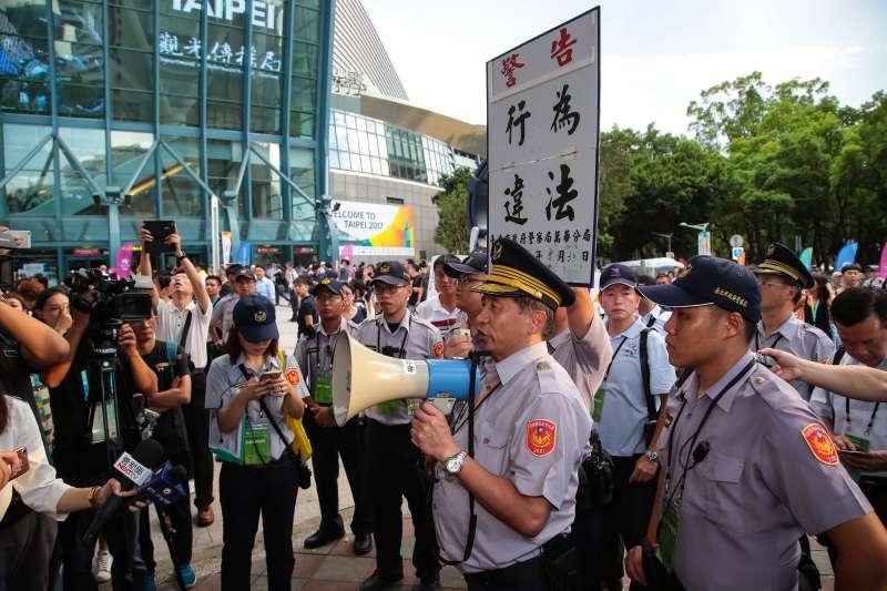 20170830-世大運30日舉行閉幕典禮,獨派團體台灣國成員於小巨蛋場館周邊發送台灣國國旗,遭警方舉牌警告。(顏麟宇攝)