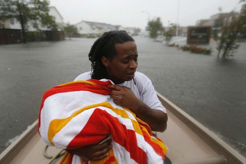 哈維颶風重創德州休士頓,釀成嚴重洪災,休士頓居民費爾(Demetres Fair)用大毛巾裹住2歲女兒,驚魂未定地隨著救難人員撤離(AP)