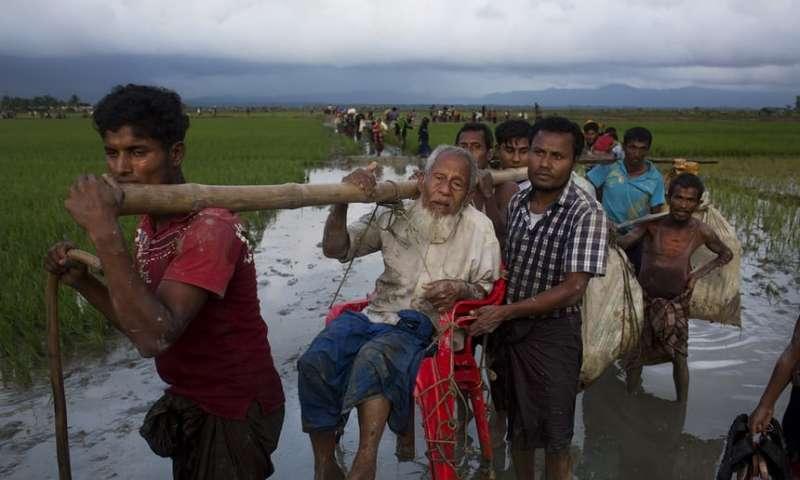 緬甸軍隊加強掃蕩,羅興亞穆斯林扁擔挑著行動不便的親人逃難。(美聯社)