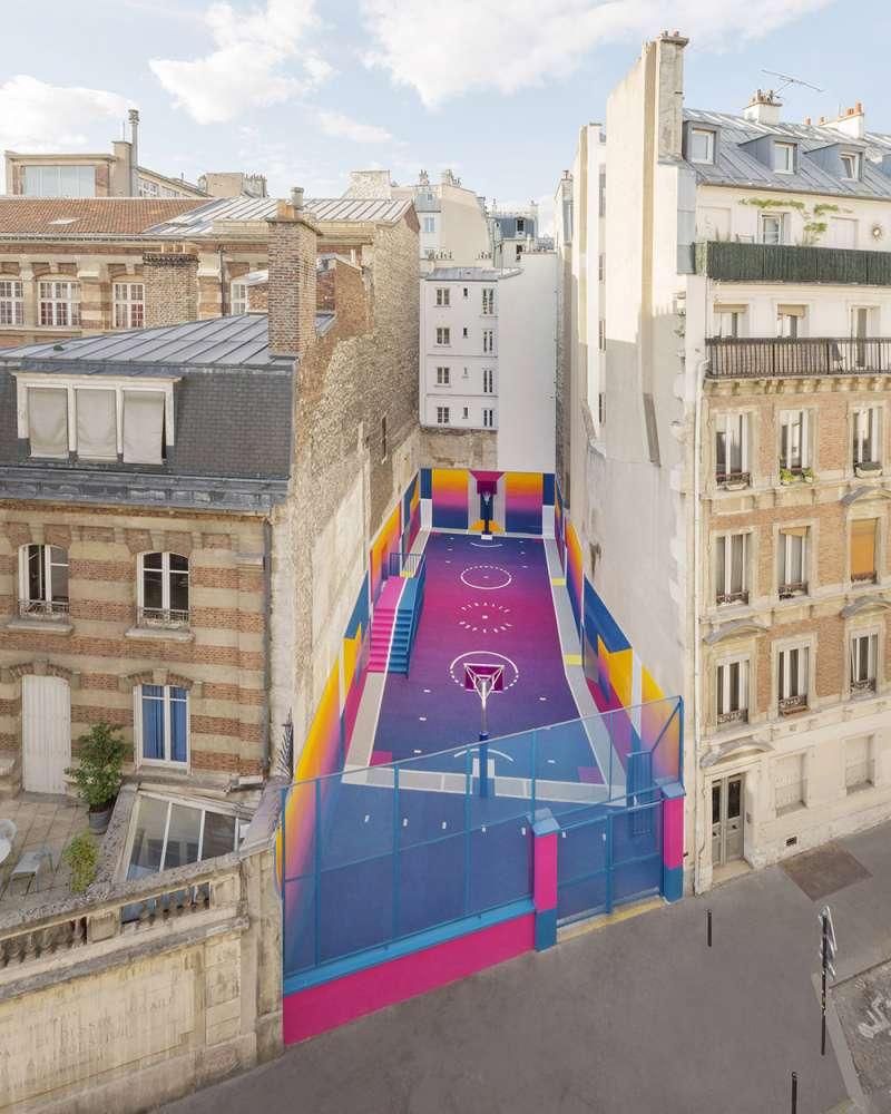 位在兩幢公寓之間的籃球場,與周圍環境形成強烈色彩對比。(圖/取自Dezeen,瘋設計提供)