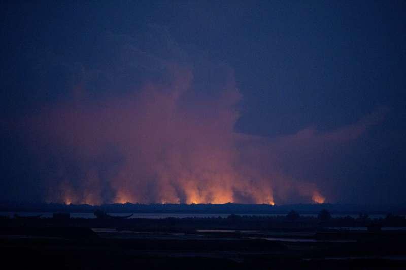 從孟加拉邊境遠望,若開邦羅興亞村莊一片火海。(美聯社)