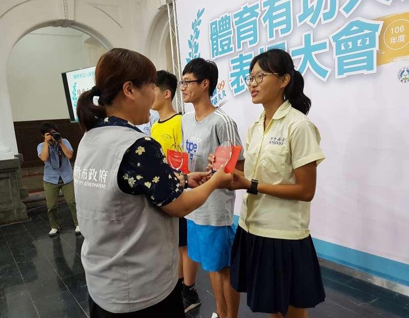為台灣首位奪下國際女子競走金牌的鄔惟喬,接受副市長沈慧虹頒獎笑臉盈人。(圖/方詠騰攝)
