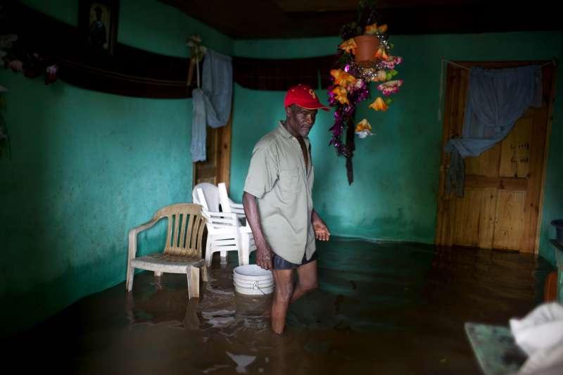 艾瑪颶風侵襲海地北部,一位災民正在檢視家裡淹水的情況(AP)