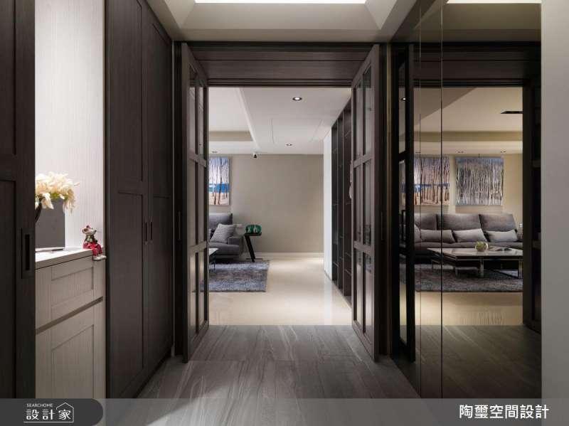 玄關右側加上銅色的穿衣鏡設計,不但隱藏了儲藏室的位置,藉由鏡面的映射效果,更讓玄關放大了兩倍。(圖/設計家Searchome提供)