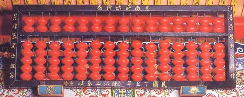 位於台南的臺灣府城隍廟,掛有一個象徵城隍爺「計算人間善惡是非」的算盤,是建築藝術的一部分,也具有警世意味。(圖/康豹提供)