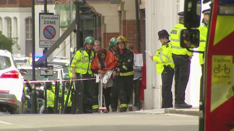英國倫敦地鐵帕森綠地站15日上午發生恐攻爆炸案,警察護送一名裹著毯子的女乘客離開車站(AP)