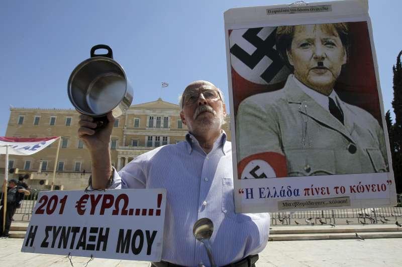 反對梅克爾的民眾將之比為希特勒。(美聯社)