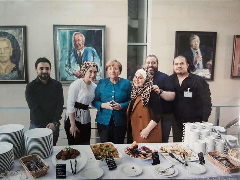 敘利亞婦女杰瑪提(右三)為逃離內戰來到德國,她在柏林展開餐飲事業,她做的中東菜連總理梅克爾(右四)也為之傾倒(取自Levante Gourmet臉書)