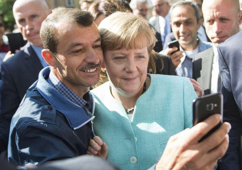 難民與德國總理梅克爾自拍。(美聯社)