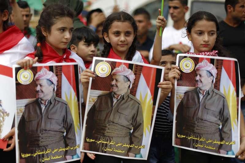 伊拉克庫德族獨立公投,庫德民眾持自治政府主席巴爾札尼的海報表示支持。(美聯社)