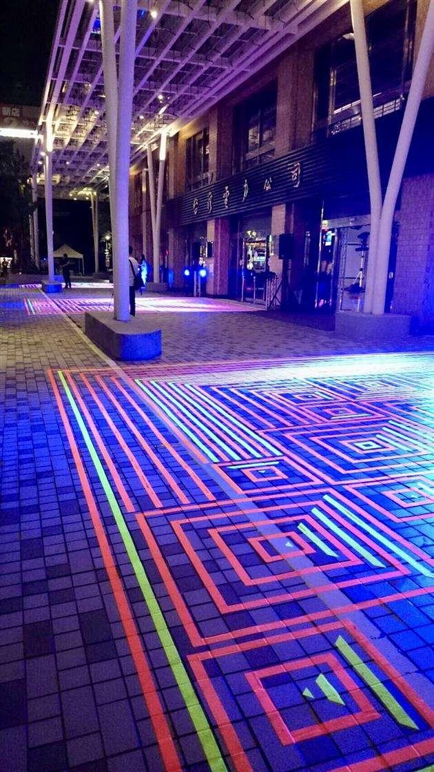 台電大樓今晚響應2017白晝之夜,由義大利藝術家打造的夜光「魔毯廣場」作品是亞洲首次展出,現場也將配上默劇及鋼琴表演,台電也特別爭取活動後保留一週,供民眾一同踏上這片夜光魔毯。(台電提供)