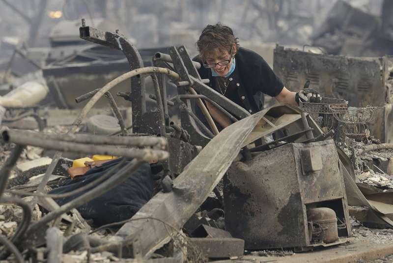 加州灣區8日起野火延燒,一位災民傷心看著淪為廢墟的家園(AP)