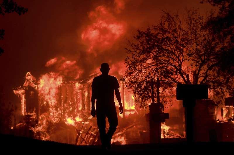 10月9日,住在加州聖羅莎方廷格羅夫(Fountaingrove)社區的一名男子望著家園被熊熊烈火吞噬(AP)