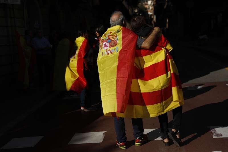 加泰隆尼亞獨立風暴持續延燒,大批民眾10月29日走上街頭,反對脫離西班牙。畫面左方男子身披西班牙國旗,右方女子身披加泰隆尼亞旗幟(AP)