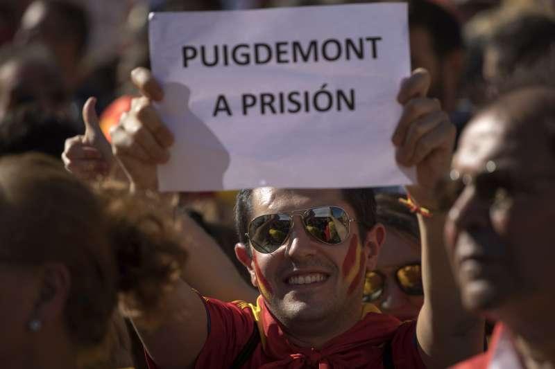 反對獨立的加泰隆尼亞民眾,29日組織萬人大遊行,標語寫著「普吉德蒙進監獄」。(美聯社)