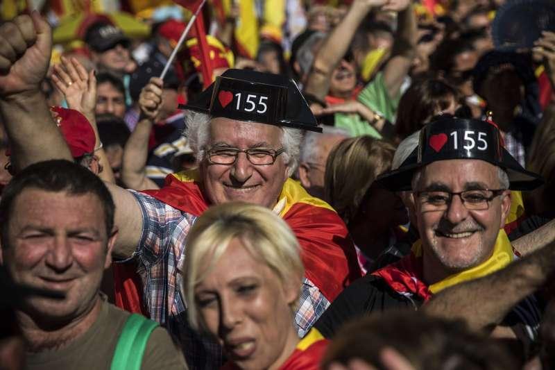 反對獨立的加泰隆尼亞民眾,29日組織萬人大遊行,民眾頭上寫著擁護反分裂的憲法第155條。(美聯社)
