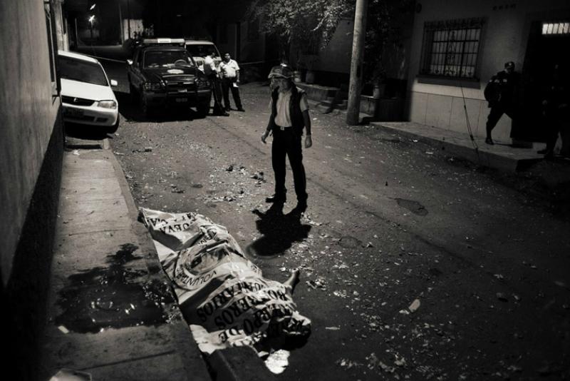 一名受害者被殺後躺在街道上。警方趕到後正在處理現場。(圖/言人文化提供)