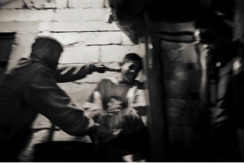 照片里一名殺手用槍抵住 Luis Esteban 的脖子,讓他還錢。這些年輕的殺手需要得到別人的敬畏,他們便去威脅、恐嚇公車司機或是小商人。(圖/言人文化提供)