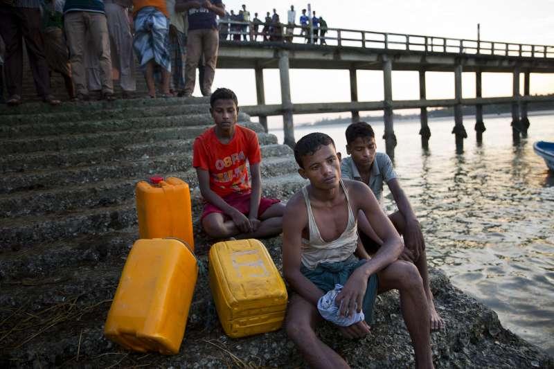 11月4日,3名羅興亞難民靠著黃色塑膠桶度過納夫河,抵達孟加拉,18歲的卡馬爾(Kamal Hussain,中)說,羅興亞人經歷許多折磨與苦難,他們渡河前想著,淹死在河裡還比較好(AP)