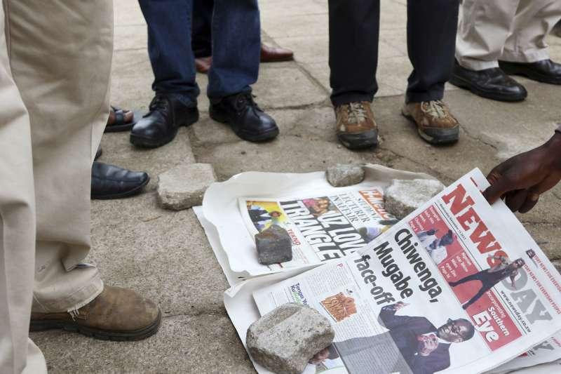 辛巴威軍隊15日進駐首都,軍人正在查看小販的報紙。(美聯社)