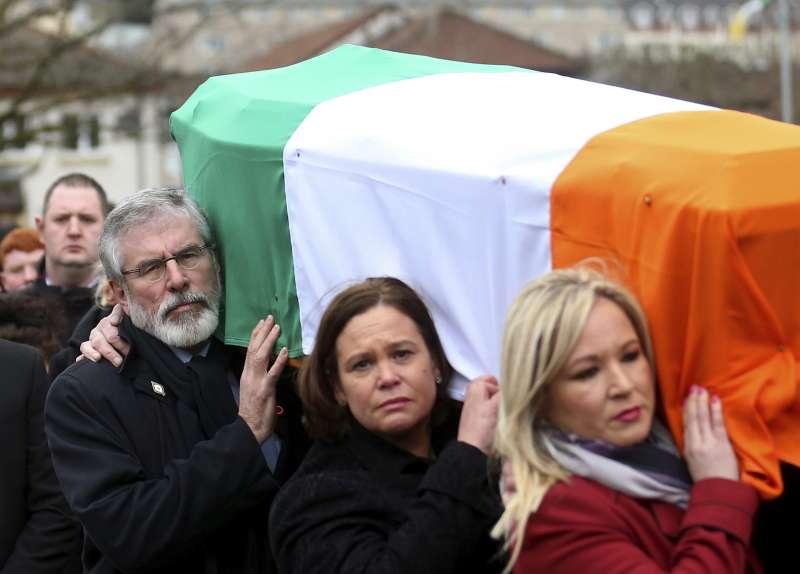 北愛爾蘭新芬黨領袖亞當斯(白鬚者)抬著摯友麥吉尼斯的棺木,兩人領導北愛爾蘭獨立運動40餘年。(美聯社)