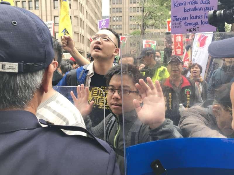 勞團及社運團體抗議勞基法修法,衝突中有民眾向警察作出舉手投降狀。(謝孟穎)