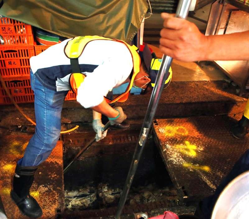 基隆市環保局清潔隊4號上午開始,清理基隆廟口水溝內的油污,清潔隊員十分辛苦。(圖/張毅攝)