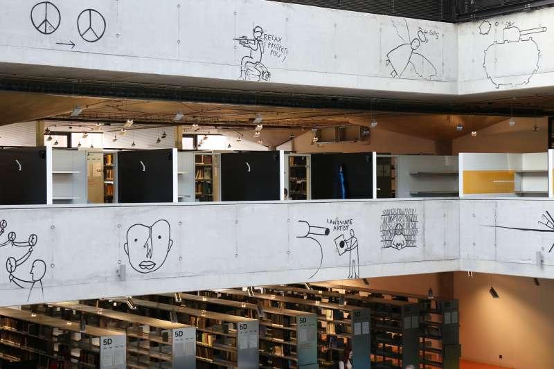 從2樓到5樓中庭周圍的鏤空牆面,布滿了羅馬尼亞籍藝術家丹•波喬韋斯奇(Dan Perjovschi)塗鴉式、漫畫風的畫作。(田中央聯合建築師事務所提供)