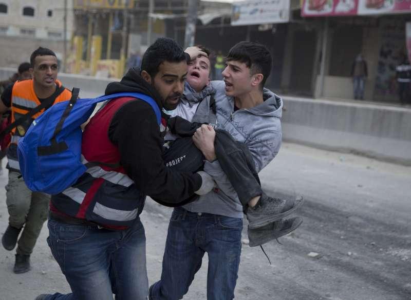 巴勒斯坦示威群眾抬走受傷的少年。(美聯社)