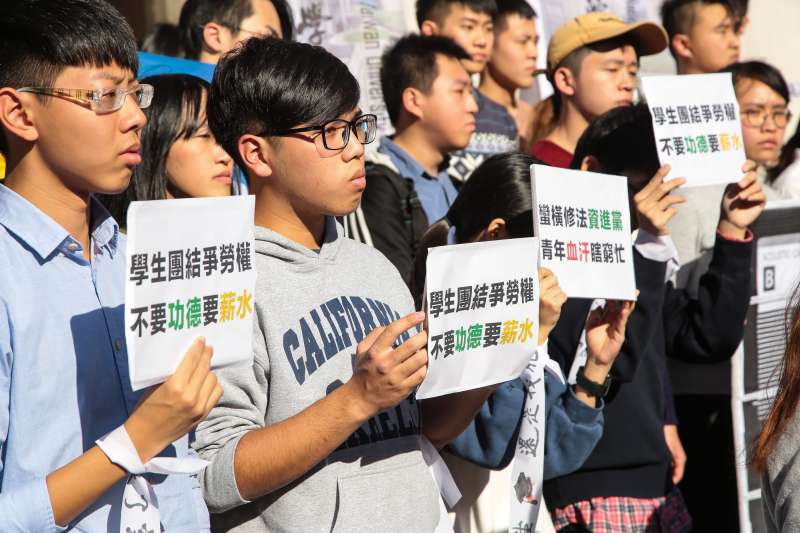 20171222-台大學生會等多個學生組織22日於立院外召開「學生團結爭勞權,反修惡法拒過勞」記者會,並舉著「學生團結爭勞權,不要功德要薪水」標語。(顏麟宇攝)