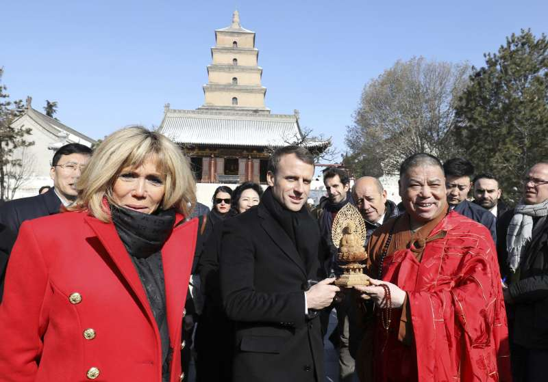 法國總統馬克宏(中)偕夫人布莉姬特(左)8日訪問中國西安的大雁塔(AP)