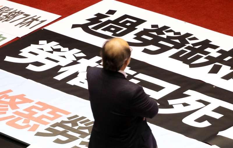 20180109-立法院臨時會預計處理勞基法修正草案。圖為民進黨總召柯建銘站在國民黨的布條前,所有所思。(蘇仲泓攝)