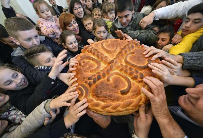 孩童搶食耶誕麵包,在麵包裡找到金幣的人可以獲得好運。(美聯社)