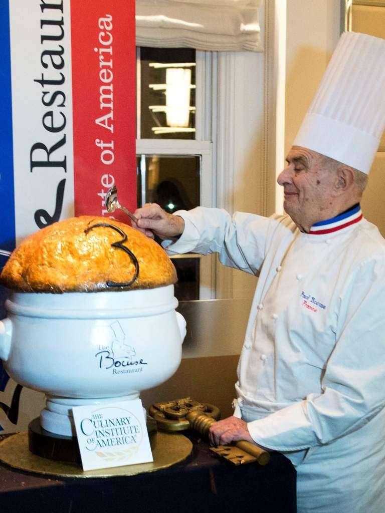 包庫斯親自示範如何把季斯卡總統黑松露清湯的酥皮敲碎 (圖/© Don Emmert  AFP,作者提供)