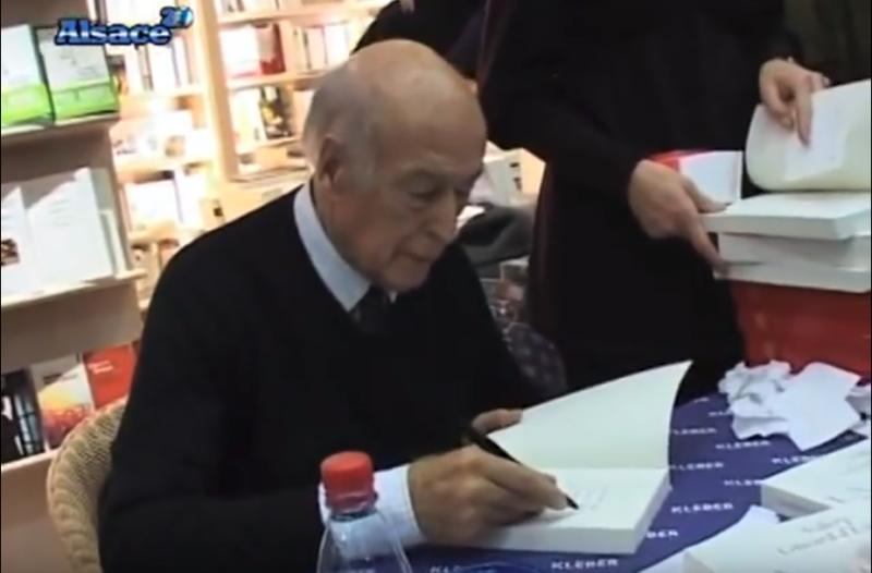 法國前總統季斯卡在為一位讀者簽名,那本書正是「王妃與總統 La Princesse et le Président」(圖/截自Youtube)