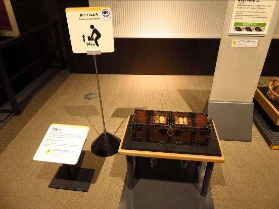拍照留念的動手操作區,並在指示牌註明金幣箱的搬動方向與重量,是相當體貼遊客的設計。攝影:路向南