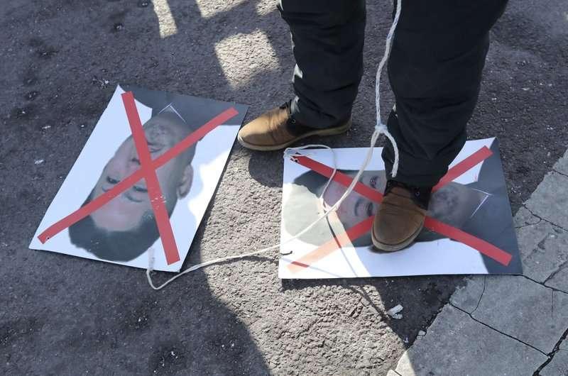 南北韓共組女子冰球隊參加平昌冬奧,有民眾在場外憤怒抗議北韓政權,踐踏金正恩相片。(美聯社)