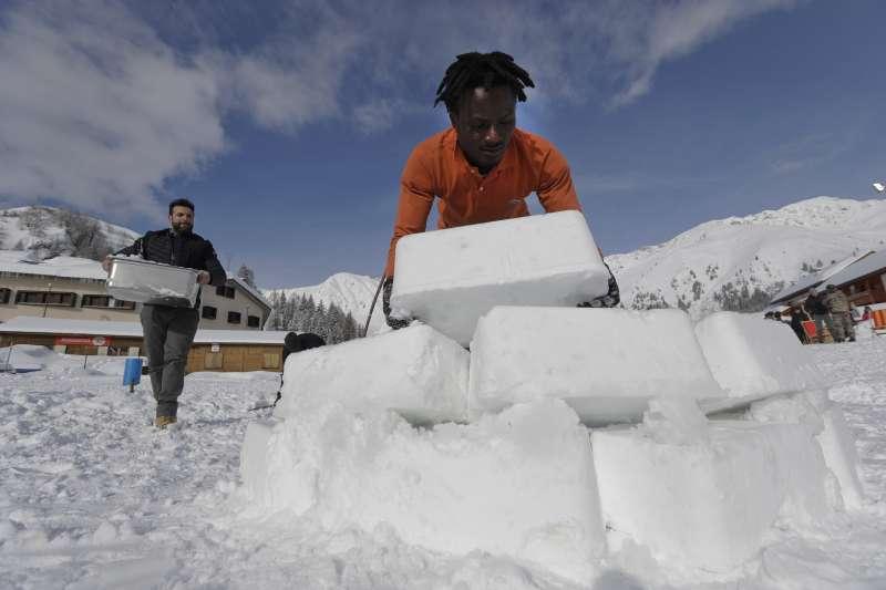 暫居聖西蒙內的非洲移民協助建造冰屋。(美聯社)