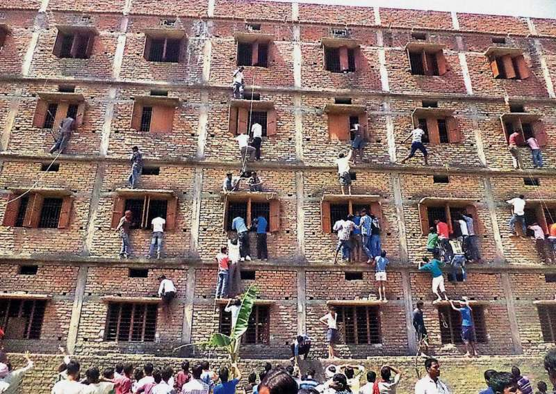 圖說:印度作弊風氣猖獗,2014年一群家長爬上建築物外牆,幫助考生作弊。