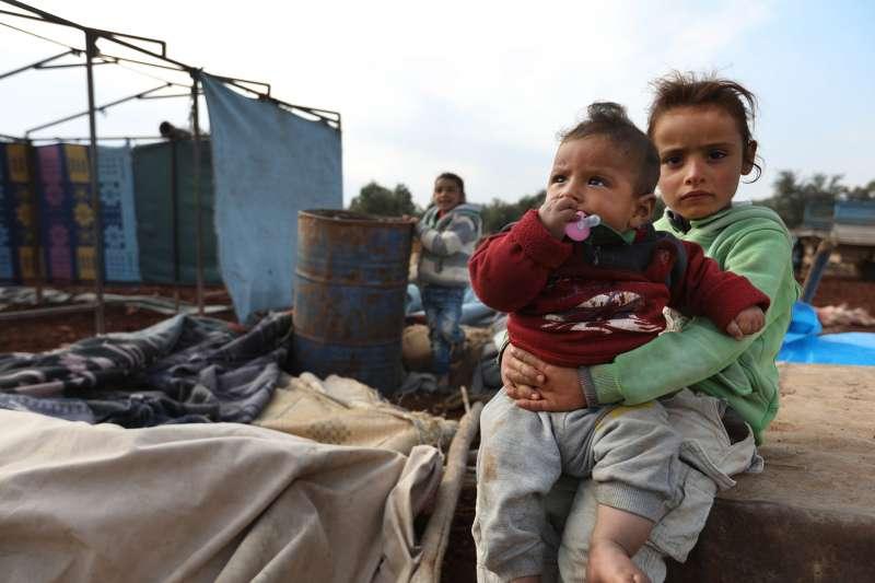 敘利亞兒童剛剛抵達新家:還未完工的臨時帳篷,但將無限期地在此棲身。逃離西北部衝突時,身上所穿的成了僅有的衣服;他們也沒有潔淨飲用水,要從生銹的桶子裡喝水。© Omar Haj Kadour/MSF
