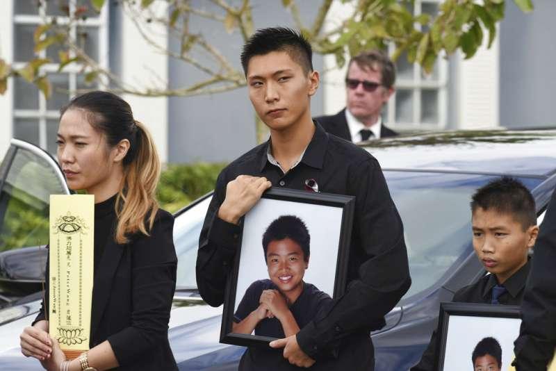 佛州校園槍擊案的15歲華裔受害者Peter Wang出殯,哥哥與弟弟分別捧著他的遺照。(美聯社)