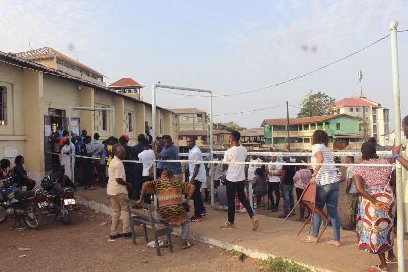 獅子山共和國於7日舉行5年一度的大選,民眾排隊進入投票所。(AP)