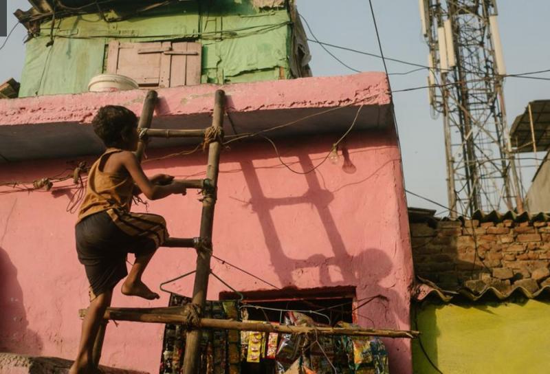 男孩和父親就住在德里的天橋下。他們將在垃圾堆裡找金屬賣錢。(圖/言人文化提供)