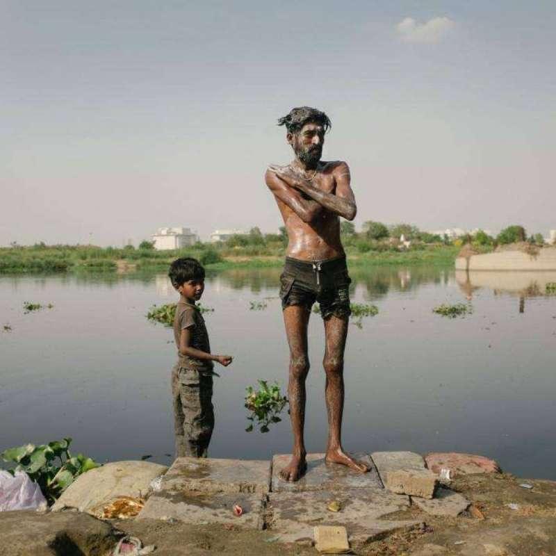 男人正帶著孩子在亞穆納河洗澡。由於高度污染,政府當局已教育人們不要在河裡洗動物。(圖/言人文化提供)