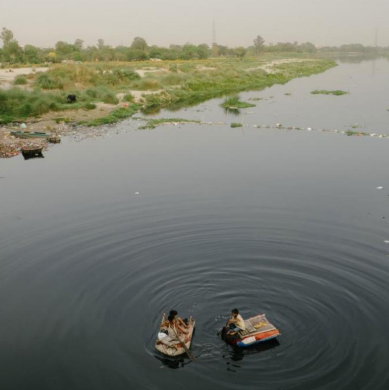 孩子們漂浮在被污染的亞穆納河上,尋找可能值錢的垃圾。(圖/言人文化提供)