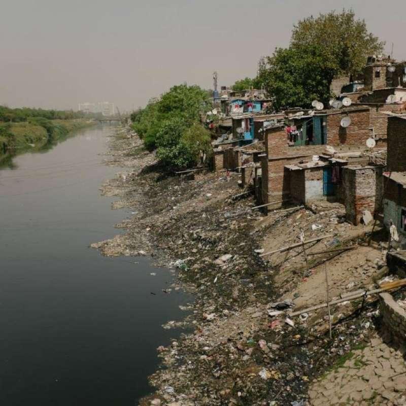 印度的貧困人口別無選擇,只能住在露天下水道旁。上圖是新德里邊緣的諾伊達地區。(圖/言人文化提供)