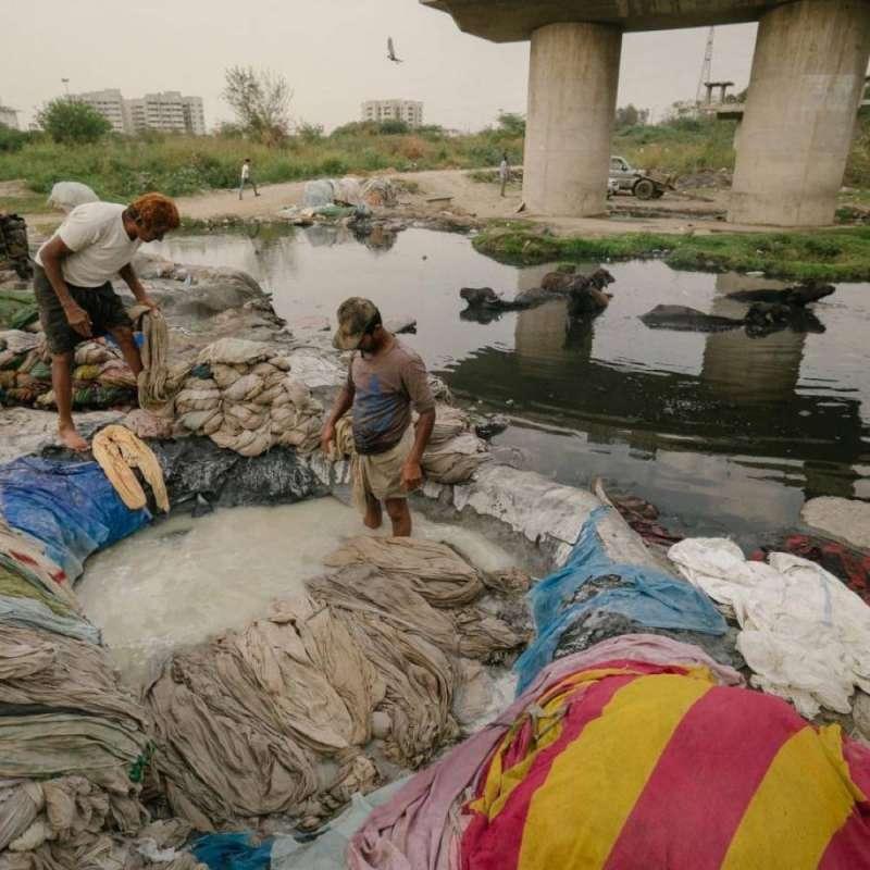 男人們正在漂洗衣服,之後會拿到被污染的亞穆納河洗「乾淨」。(圖/言人文化提供)