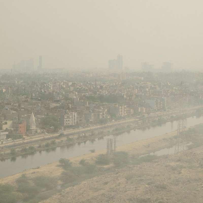 在這張拍攝於露天垃圾場上方的照片中,籠罩在德里之上的煙霧簡直讓人窒息。(圖/言人文化提供)