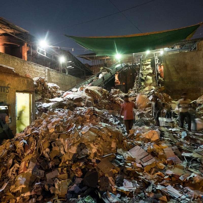 夜幕降臨,男人們仍在諾伊達地區的垃圾回收站工作著。(圖/言人文化提供)